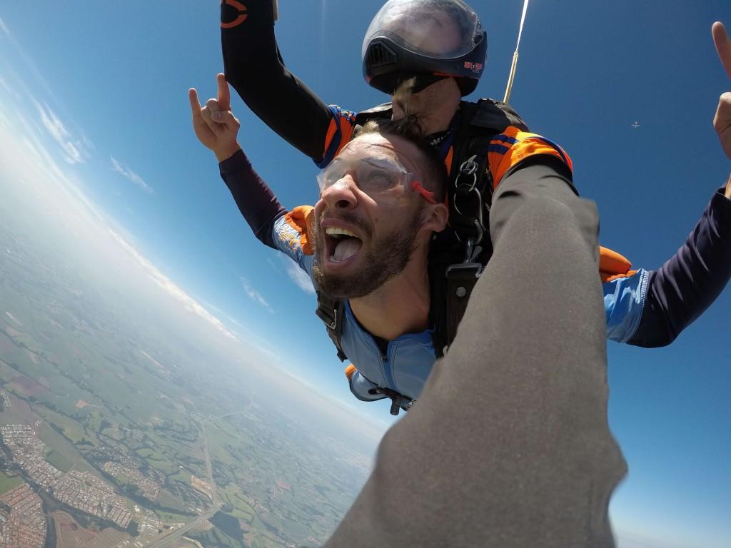 Homem no ar em salto duplo de paraquedas com instrutor