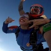 Mulher saltando de paraquedas com o instrutor