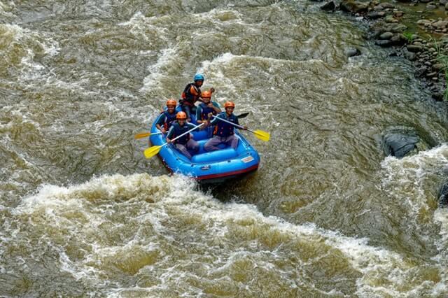 A imagem mostra 5 pessoas em um bote praticando rafting