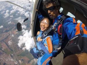 Menina em salto de paraquedas com instrutor