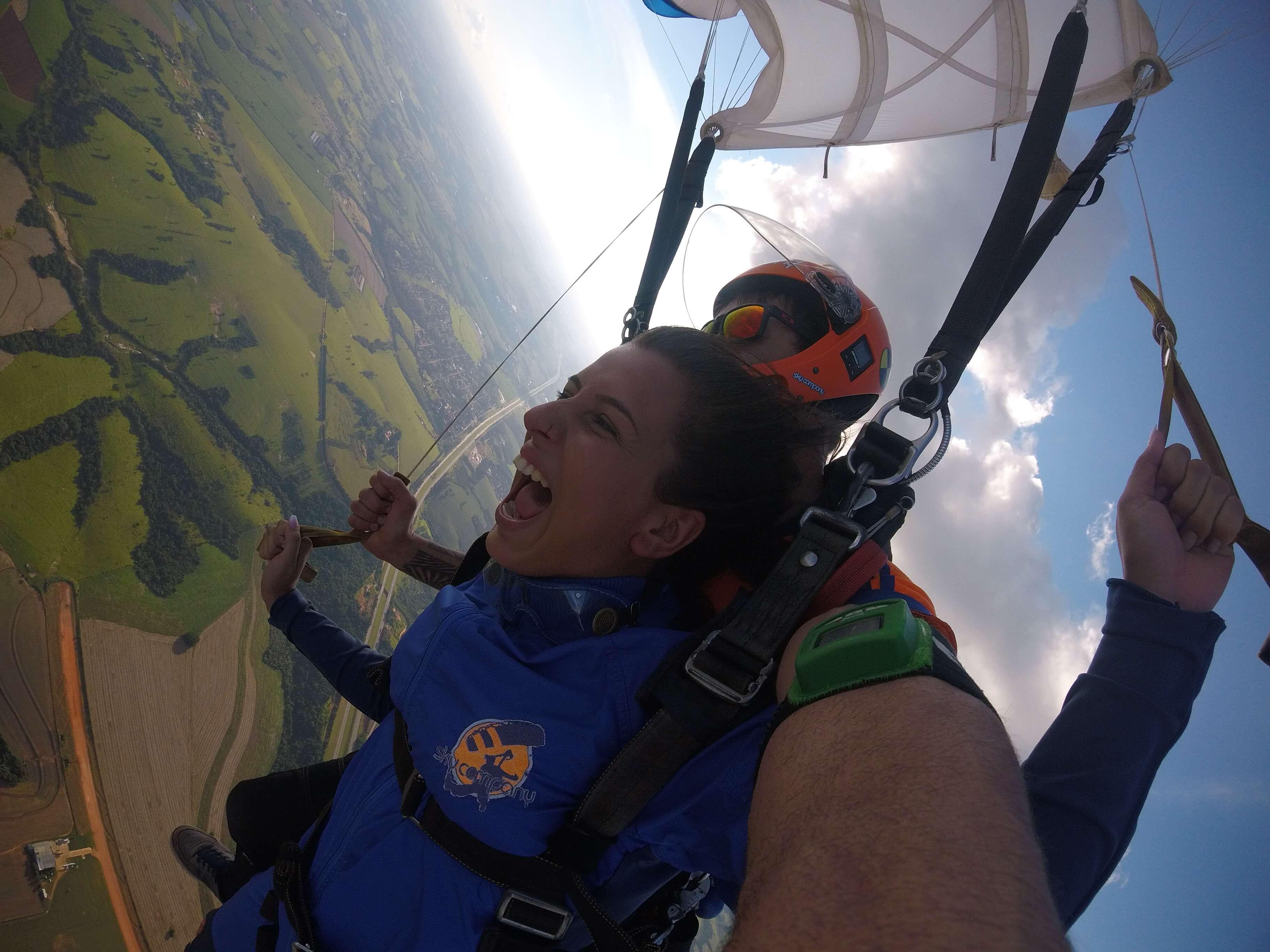 Mulher acompanhada de instrutor saltando de paraquedas