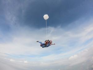 Pessoa saltando de paraquedas em céu azul