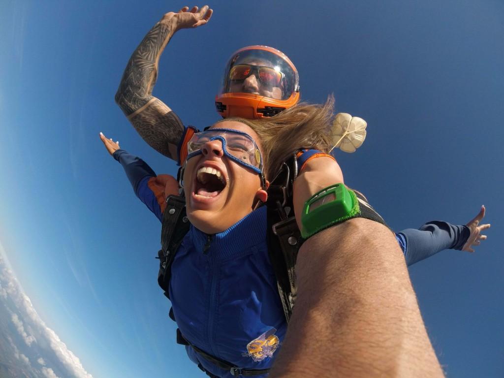 Homem e mulher em queda livre no salto duplo de paraquedas