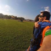 Casal se abraçando após salto de paraquedas