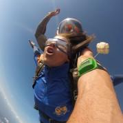 Mulher realizando salto de paraquedas com instrutor