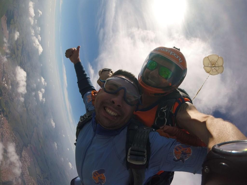 Pessoa saltando de paraquedas por presente radical