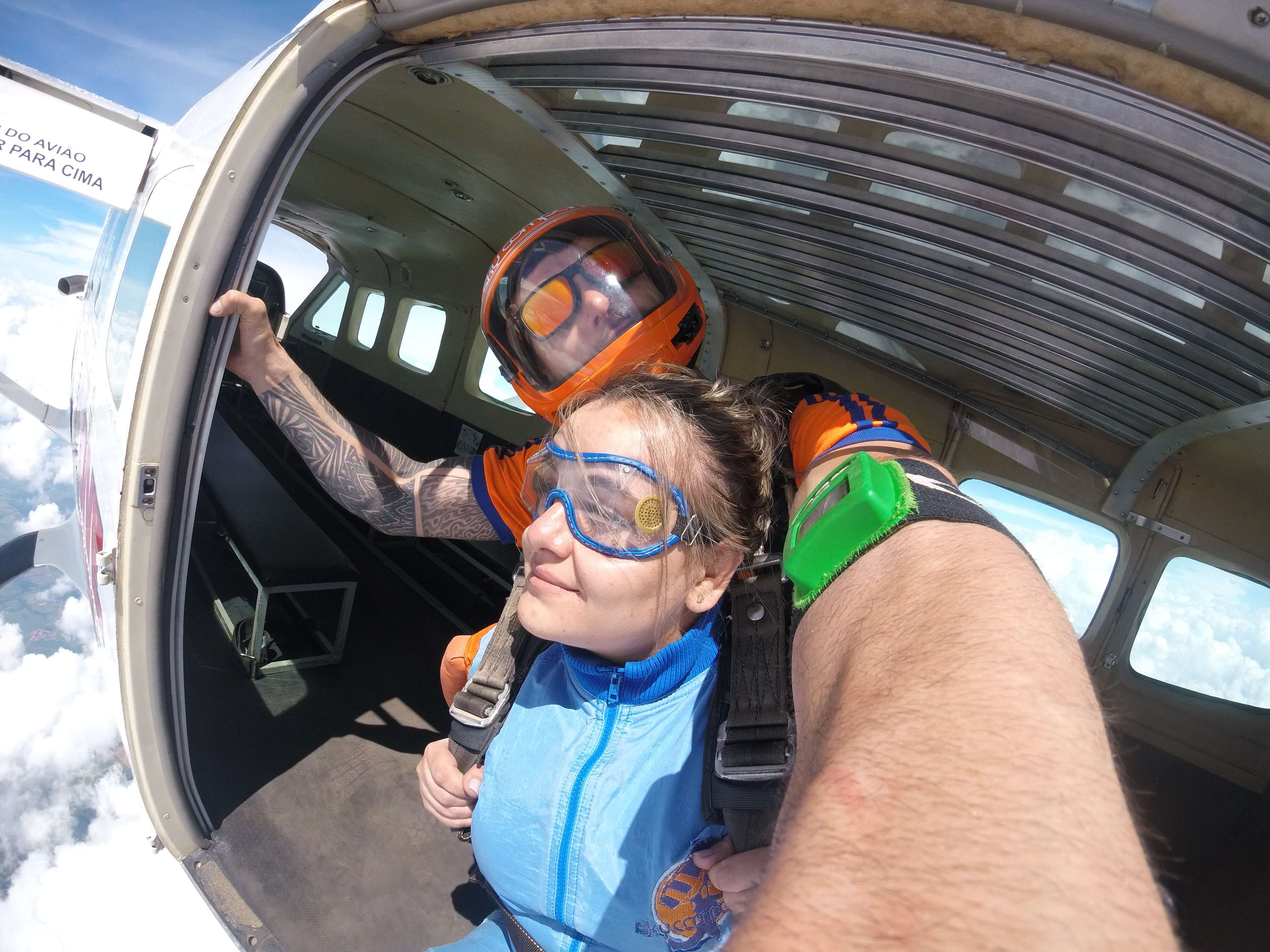 Mulher saltando de paraquedas com instrutor
