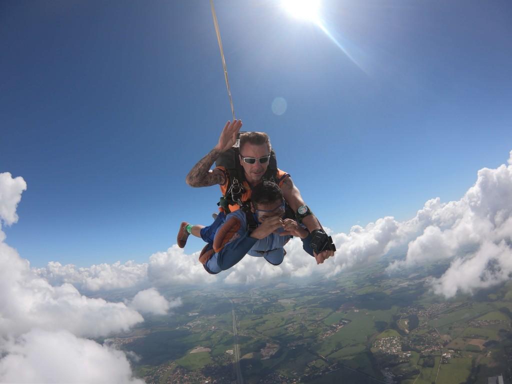 Homem saltando de paraquedas com instrutor