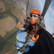 Mulher pousando de paraquedas com instrutor