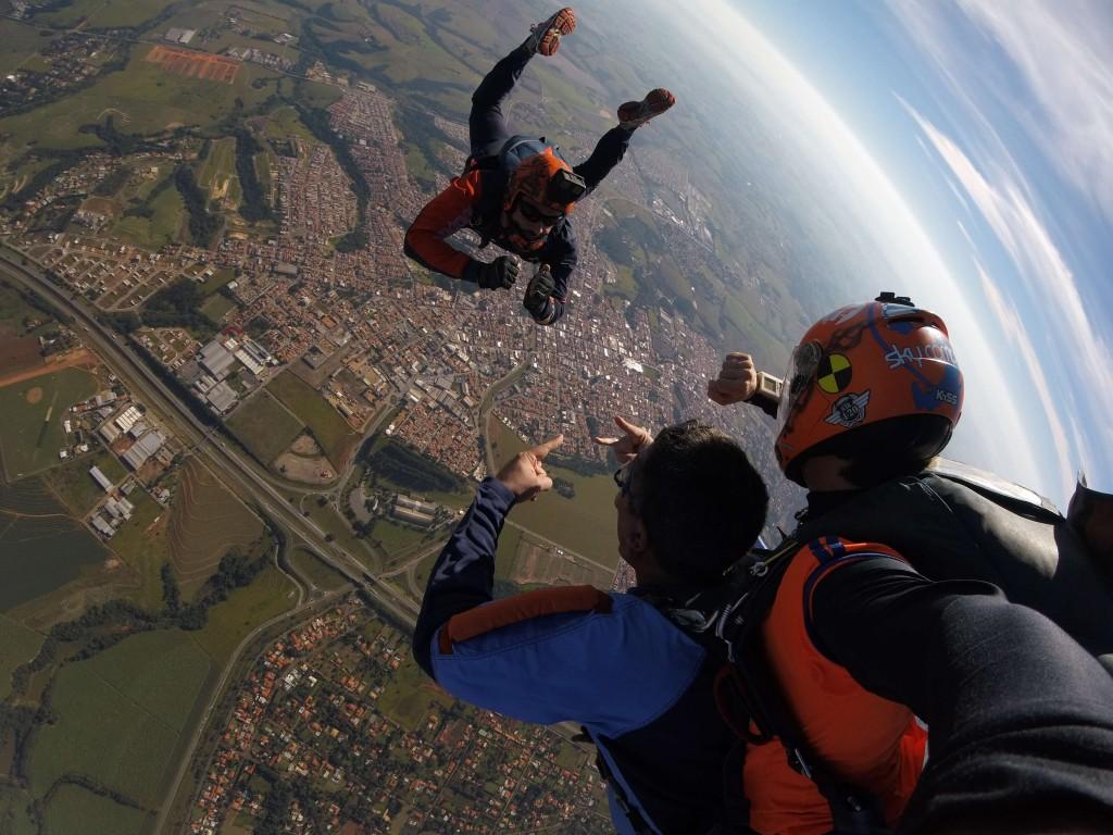 Três pessoas saltando de paraquedas