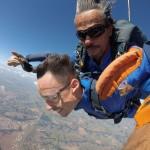 Rapaz saltando de paraquedas com instrutor