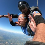 Mulher com instrutor em salto de paraquedas