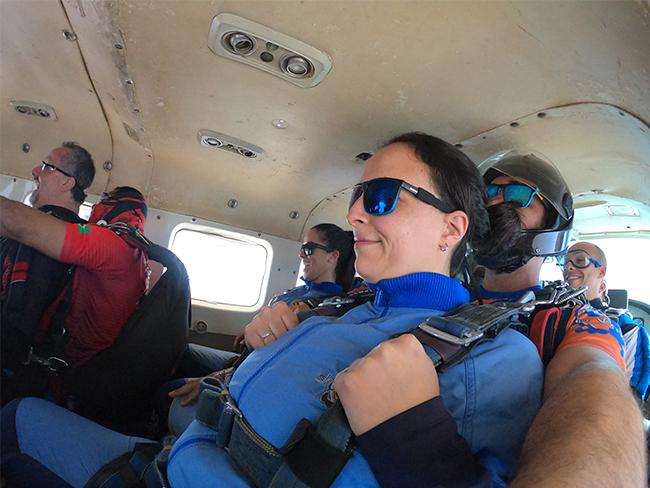 cliente saltando de paraquedas ao lado de instrutor dentro de helicóptero